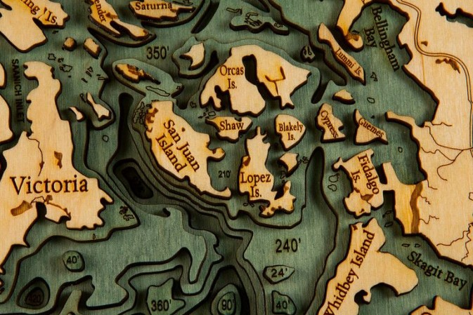 Below the boat, des cartes sous-marines en relief, découpées au laser